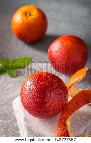 Three blood oranges on stone background closeup