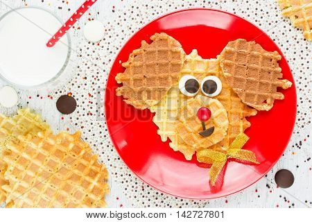 Sweet waffles with chocolate and milk for baby breakfast. Creative idea for children fun dessert or breakfast - puppy dog shaped waffles food art for kid