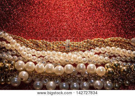 Close up of luxury beautiful jewelry on a red shiny glitter background.