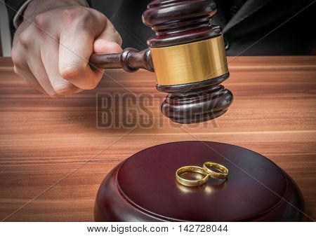 Divorce concept. Hand of judge in courtroom is holding gavel. Wedding rings in front.