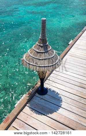 Lamp on the wooden jetty over blue water in suny day. Maldives