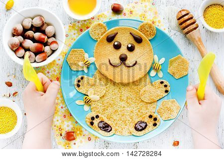 Pancakes for baby breakfast. Bear pancakes with honey and nuts - creative idea for children breakfast or dessert funny food art for kids edible picture on a plate top view