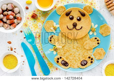 Bear pancakes with honey and nuts - creative idea for children breakfast funny food art for kids edible picture on a plate top view