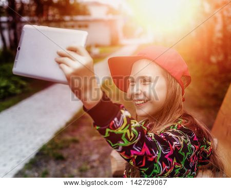 Beautiful teenage girl taking a selfie on smartphone outdoors in park on sunny autumn day.