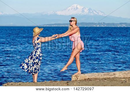 Mother and daughter on beach. Centennial Beach at Boundary Bay Regional Park Tsawwassen British Columbia Canada.