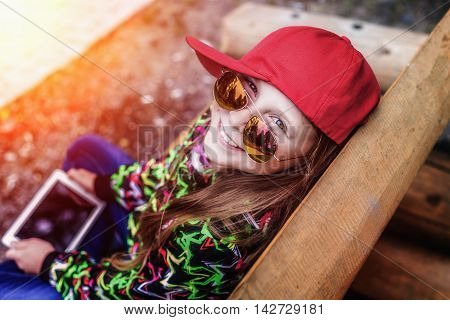 Beautiful young girl relaxing with the tablet in the autumn park.