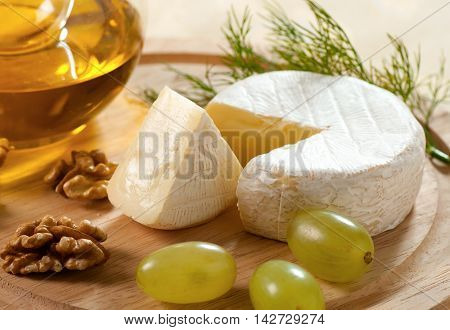 Brie cheese with grapes and walnuts still-life