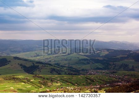 landscape consisting of a Carpathians mountains with fir-tree and green grassy valley with houses and sky with blue clouds on the background