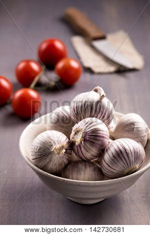 Bowl of chinese solo garlic without cloves, tomatoes and knife on wooden background