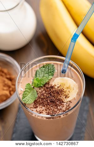 Glass of chocolate banana smoothie with straw top view