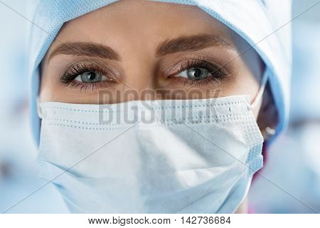 Close up portrait of adult female surgeon doctor wearing protective mask and cap. Surgeon in operation theatre. Healthcare medical education emergency medical service and surgery concept