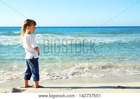 happy little girl in the sand on the beach