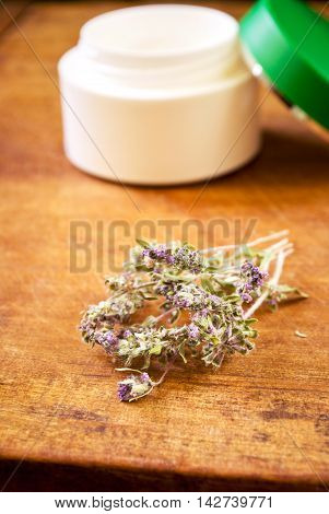 Organic cream mask with herbs on a wooden table