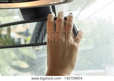girl with beautiful manicure in car regulates  rear view mirror