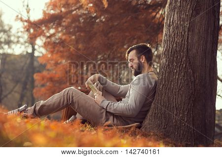 Young handsome man sitting on a fallen autumn leaves in the park reading a map getting ready for a travel adventure