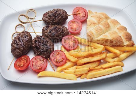 Kofta kebab, minced meat skewer with pita bread and french fries