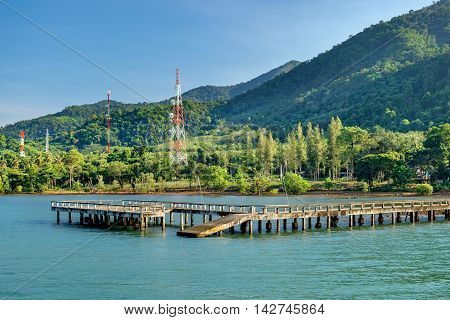 Port ferry boat with concrete ferry pier. Travel inspiration. Tropical landscape over sea with cloudy bright sky Koh Chang island Thailand.