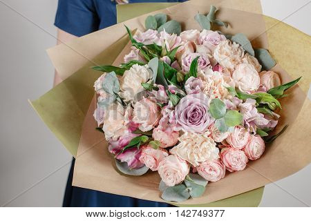 Florist girl with rich bunch flowers. Fresh spring bouquet. Summer Background. Young woman with flower bouquet for birthday or mother's day.