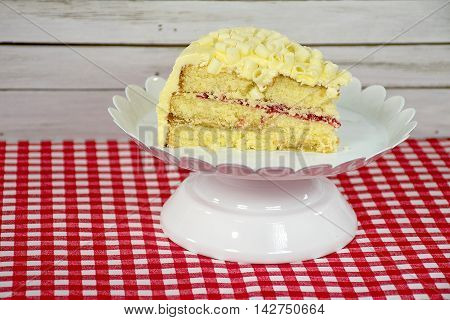 Lemon cake slice on pedestal plate with raspberry filling and white chocolate curls