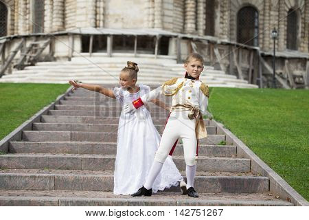 Childrens ballroom dance couple in suits, summer outdoors