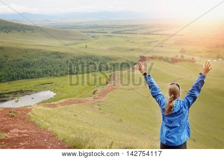 Rear View Of Woman Standing On Mountain With Arms Outstretched.