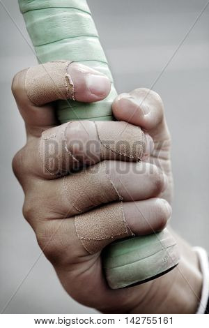 bandage on a boys finge, holding a tennis racket