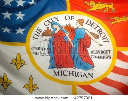 This detail of the flag of the City of Detroit, Michigan portrays its founding by the French in 1701, the subsequent presence of the British, and the 13 stars and red and white stripes of the original colonies of the United States. The seal in the center