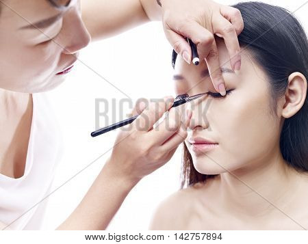makeup artist working on a beautiful young female asian model isolated on white background.
