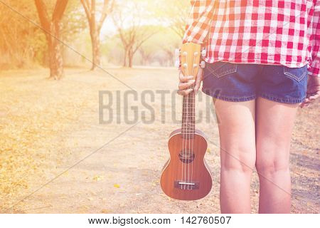 Beautiful asian woman holding ukulele guitar at outdoor in pastel and vintage style color. copy space background