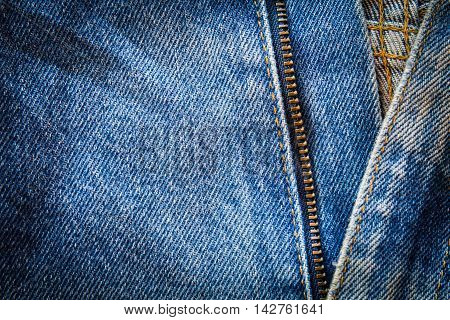 Close up of blue jeans fabric with seam and zipper. select focus