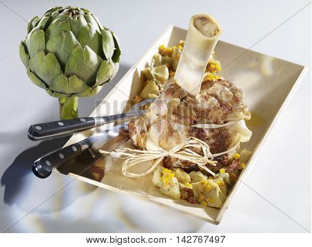 Veal Shank braised way barigoule with artichoke on wooden plate