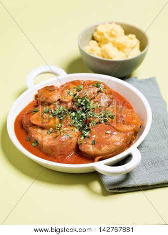 Osso buco con gremolata or Veal Shank Milanese on white plate in restaurant