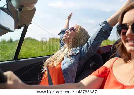 summer holidays, road trip, vacation, travel and people concept - smiling young women driving in in cabriolet car