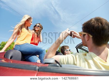 leisure, road trip, travel and people concept - happy friends driving in cabriolet car and taking picture by smartphone