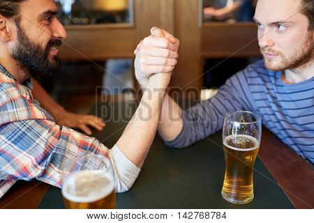people, leisure, challenge, competition and rivalry concept - happy male friends arm wrestling and drinking draft beer at bar or pub