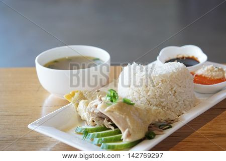 Chicken rice with sliced cucumber bowl of soup soyal and chili sauce on white plate