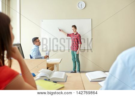 education, school, learning and people concept - student boy showing something on blank white board and teacher in classroom