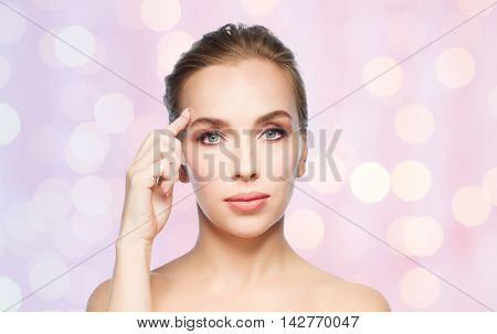 beauty, people and plastic surgery concept - beautiful young woman showing her forehead over rose quartz and serenity lights background