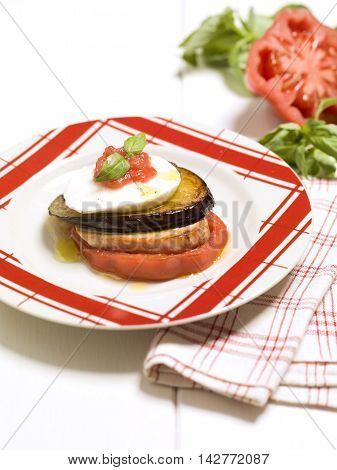 Veal Parmigiana with eggplant and tomatoes on white plate in restaurant