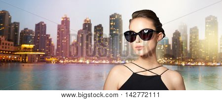 accessories, eyewear, fashion, people and luxury concept - beautiful young woman in elegant black sunglasses over dubai city night lights background
