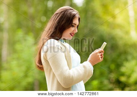 Beautiful girl in a white jacket looks at the phone screen and smiles.Internet and hanging out