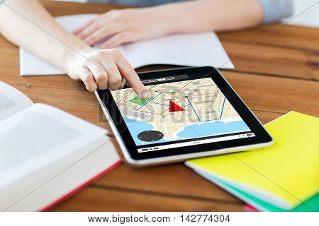 business, education, technology and location concept - close up of student woman with gps navigator map on tablet pc computer screen and notebook at home with gps navigator map on screen