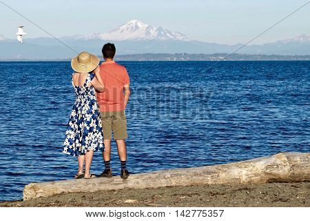 Man and woman on beach by blue sea. Centennial Beach at Boundary Bay Regional Park Tsawwassen British Columbia Canada.