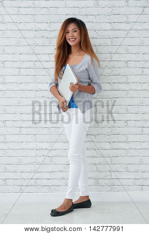 Full-length portrait of attractive Filipino woman with laptop