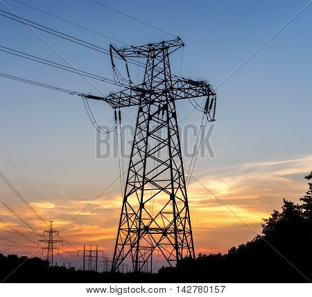 Electric pole connect to the high voltage electric wires on sunset sky background