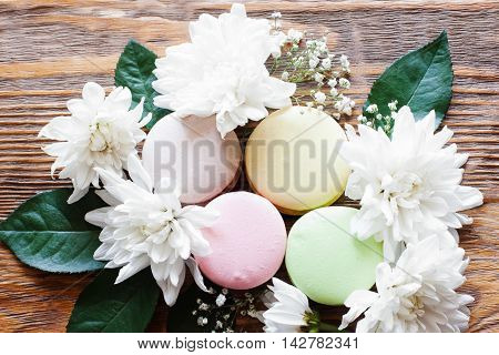 Sweet closeup photo of french traditional cookies. Lovely macaroon with flowers on the wooden background.