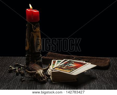 Still life with magic objects, evil candles. Fortune telling seance or black magic ritual. Scary still life with tarot.