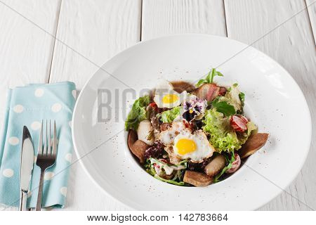 Salad with tongue and quail eggs on white wooden background. Restaurant serving of meat side dish with cutlery, armenian cuisine