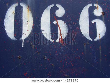 El número 066 cero sesenta y seis rociado en blanco en una placa de Metal oxidado azul