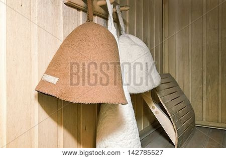 The interior of a small Finnish sauna with wooden walls. On the wall hang hats made of felt for a bath.